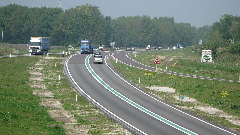 Een weg met een groene strook.