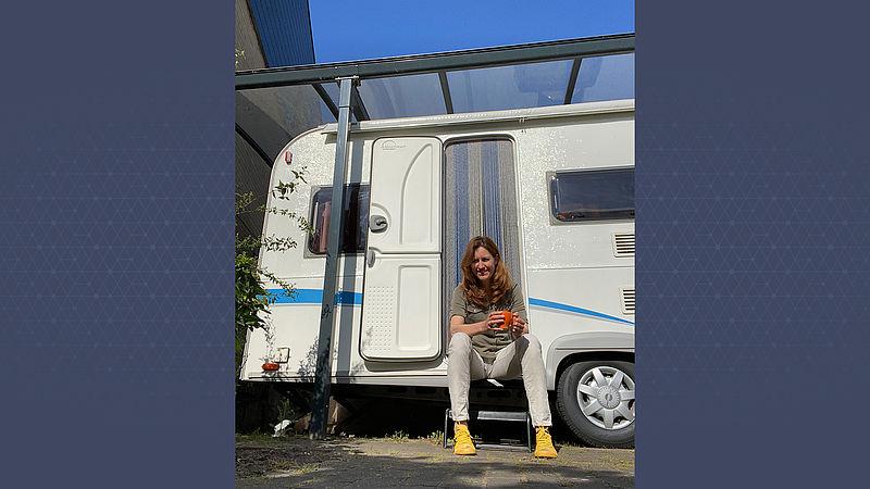 Ingrid op het trapje van de caravan
