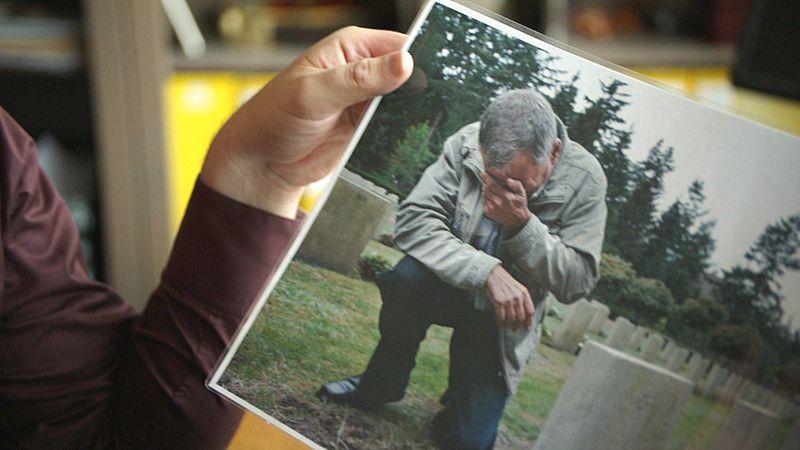 Een foto van een nabestaande bij een van de graven