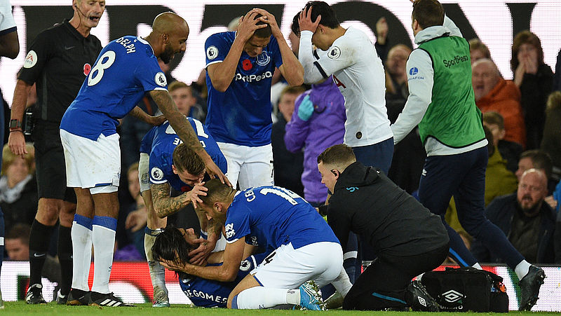 Evertons middenvelder André Gomes ligt geblesseerd op de grond