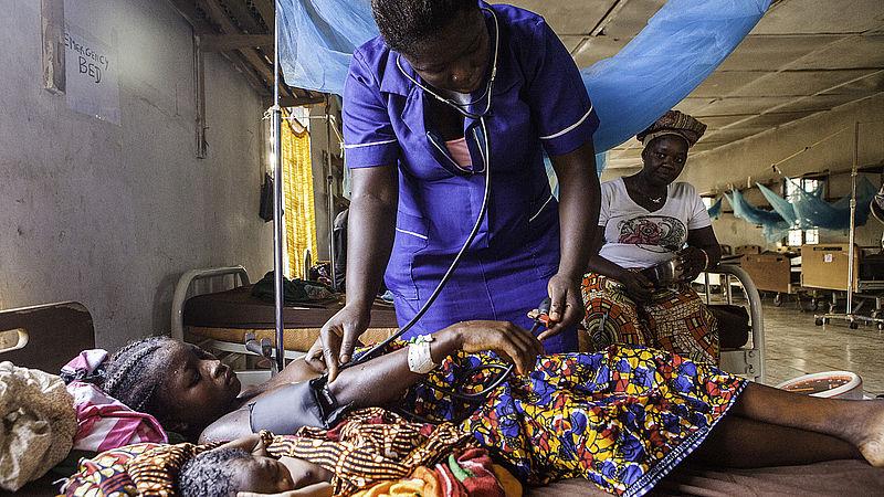 Verpleegster neemt hartslag op bij patiënt in ziekenhuis in Sierre Leone
