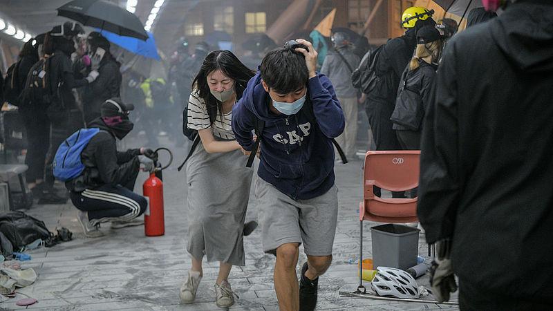 Demonstranten zoeken dekking voor traangas