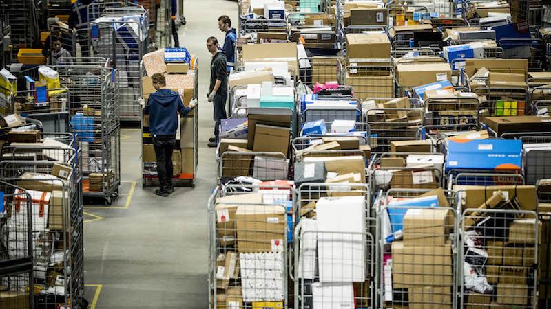 Medewerkers van PostNL sorteren pakketjes in het pakkettensorteercentrum.